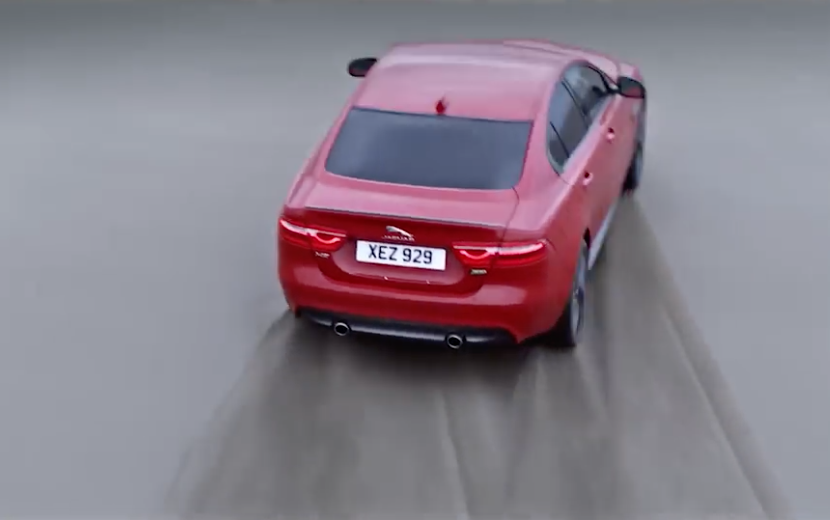 Jaguar XE 300 Sport in red is seen from above, close-up from above doing a power slide on a beach.